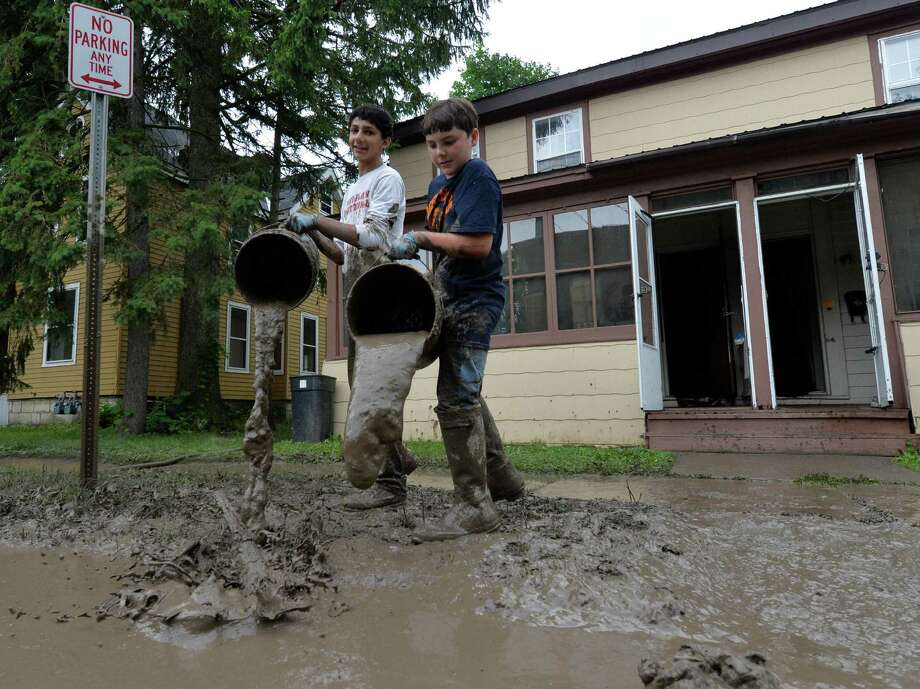 Christopher Shariff, 13, left, and his friend Connor Shults, 12, carry buckets of mud from the basement of a flooded home on Willett Street on Monday, July 1, 2013,  in Fort Plain, N.Y. (Skip Dickstein/Times Union) Photo: SKIP DICKSTEIN / 00023010A