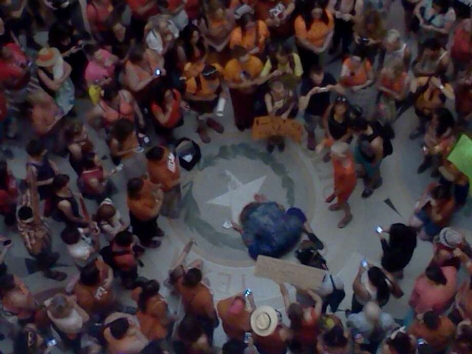 A woman kneels in the middle of the rotunda, to the applause of the pro-life supporters around her. The crowd goes silent, and begins to chant once more. Photo: Emily Bamforth Photo: Express-News