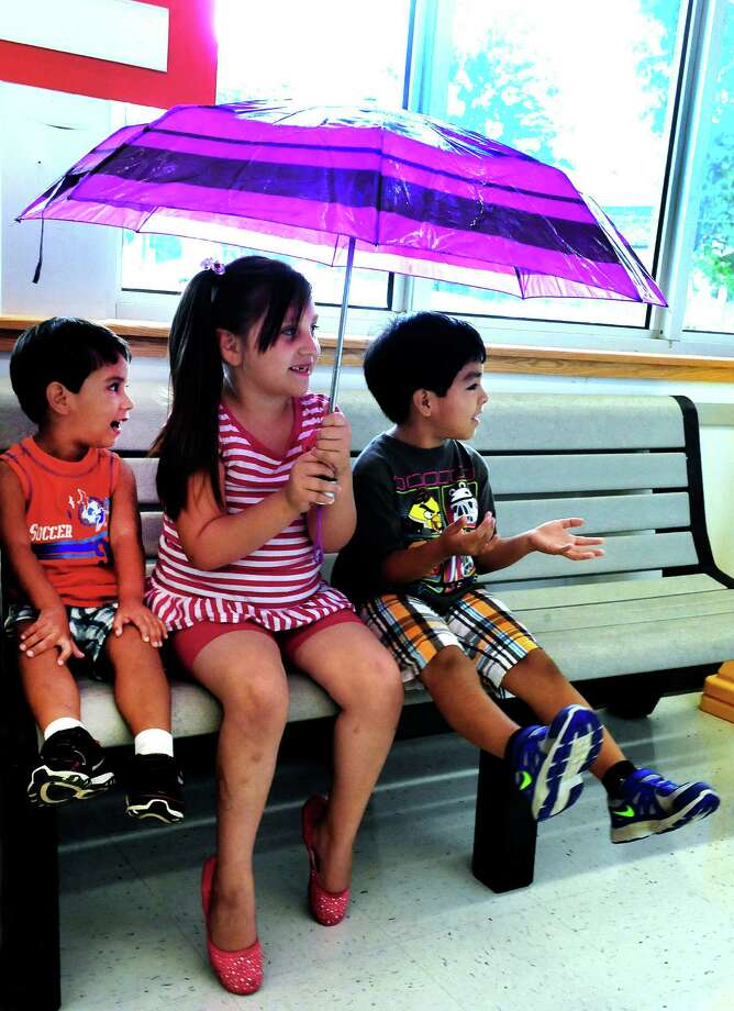 Christopher Iniguez, 3, left, his sister, Daniella, 7, and Justin Vargas, 6, wait for their mothers inside the PriceRite supermarket in Danbury, Conn. Monday, July 1, 2013. Photo: Michael Duffy / The News-Times