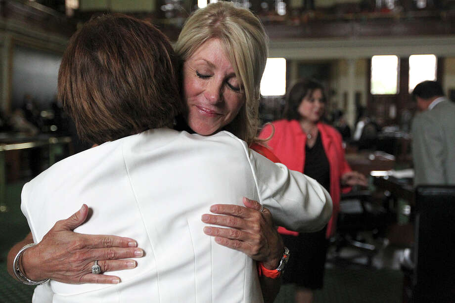 Senator Wendy Davis, D-Fort Worth, hugs Annabelle Garcia, sister of Sen. Leticia Van de Putte, D-San Antonio in back, after the Texas Legislature adjourned on the first day of a second special session, Monday, July 1, 2013. Davis was expressing her condolences for the death of Daniel San Miguel, father of the sisters. Photo: Jerry Lara, San Antonio Express-News / ©2013 San Antonio Express-News