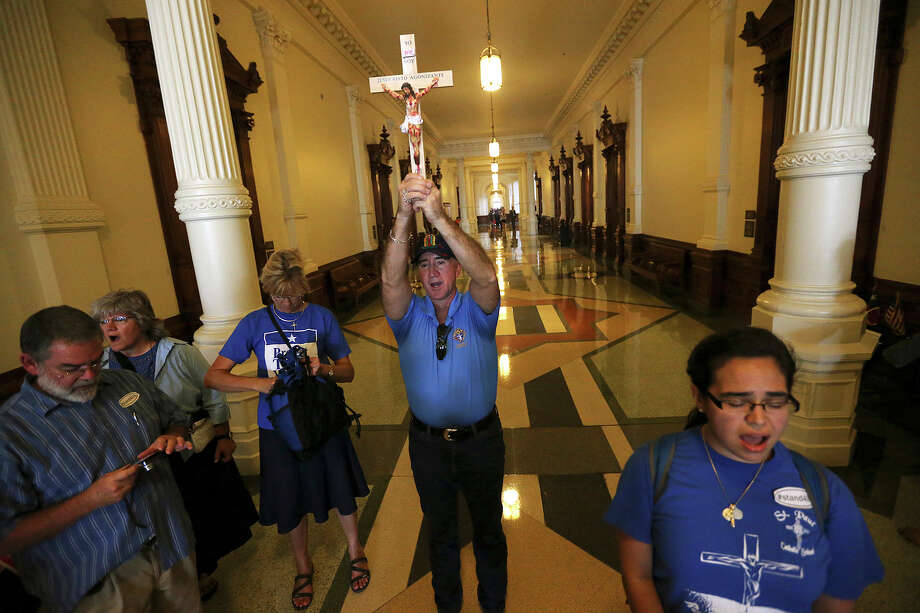 Matt Benavides, with the Archdiocese of San Antonio, holds a crucifix while leading a group of an anti-abortion bill supporters at the State Capitol, Monday, July 1, 2013. It was the start of the second legislative special session. Photo: Jerry Lara, San Antonio Express-News / ©2013 San Antonio Express-News