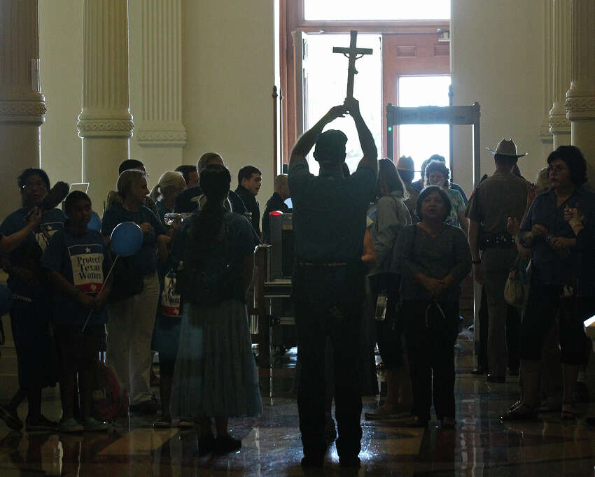 Matt Benavides, with the Archdiocese of San Antonio, holds a crucifix while leading a group of an anti-abortion bill supporters at the State Capitol, Monday, July 1, 2013. It was the start of the second legislative special session.