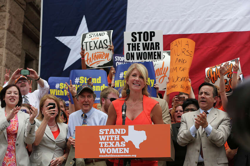 Senator Wendy Davis, at podium, smiles as she is introduced as the main speaker at the Stand With Texas Women Rally at State Capitol before the start of the second special session, Monday, July 1, 2013. The anti-abortion legislation rally drew thousands of supporters. To the right is Sen. Carlos Uresti, D-San Antonio.