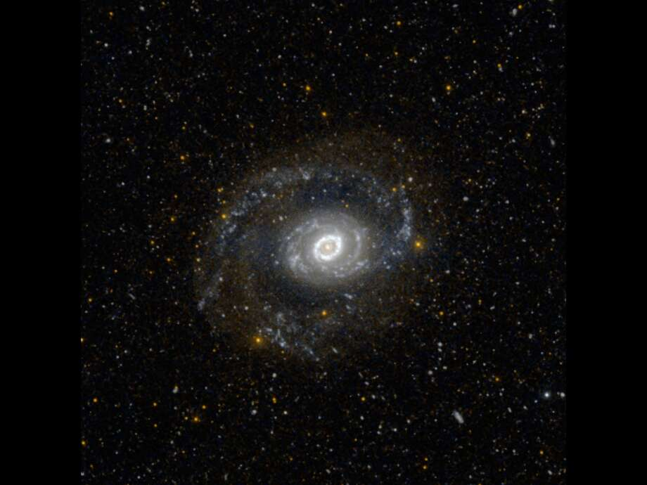 This image from NASA's Galaxy Evolution Explorer shows Messier 94, also known as NGC 4736, in ultraviolet light. It is 17 million light-years away in the constellation Canes Venatici.Astronomers think the galaxy's oval shape may be responsible for the distinctive ring of stars at its center. The young stars in the ring glow with ultraviolet light, so they appear bright to GALEX's detectors.Blue-white regions in the galaxy's outer arms highlight areas of current star formation. Diffuse faint red light is from regions where star formation ceased more than 100 million years ago. Photo: NASA/JPL-Caltech