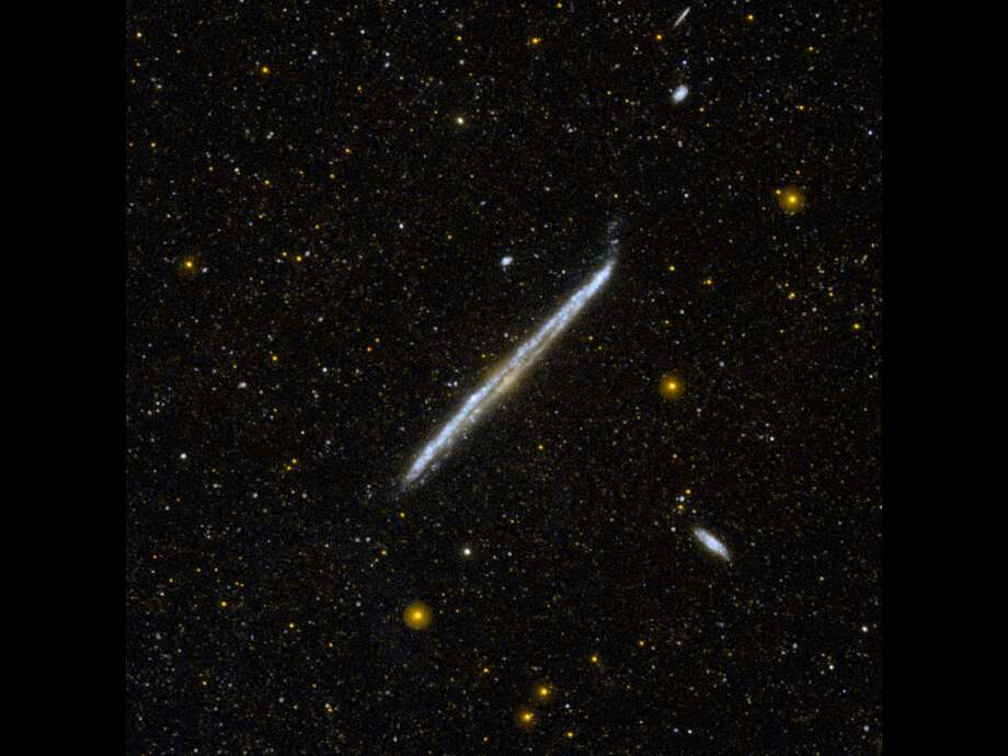 This image from NASA's Galaxy Evolution Explorer shows NGC 4565, one of the nearest and brightest galaxies not included in the famous list by 18th-century comet hunter Charles Messier.The galaxy is 30 to 50 million light-years away, in the constellation of Coma Berenices. It is more luminous than the Andromeda galaxy, and would be one of the most spectacular galaxies in the sky if we had a face-on view, rather than edge-on. Photo: NASA/JPL-Caltech