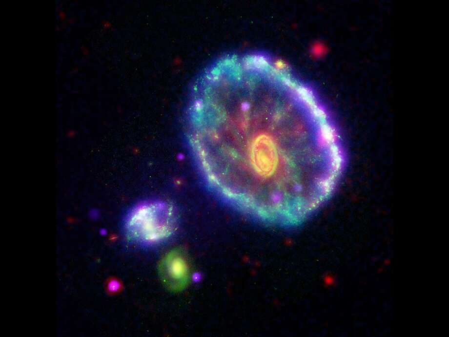 This image of the Cartwheel galaxy shows a rainbow of multi-wavelength observations from NASA missions, including the Galaxy Evolution Explorer (blue), the Hubble Space Telescope (green), the Spitzer Space Telescope (red) and the Chandra X-ray Observatory (purple). Photo: NASA/JPL-Caltech
