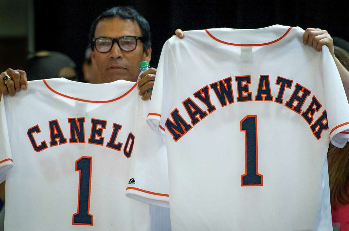 Former Houston Astros player Jose Cruz holds up a team jersey bearing the name of boxer Canelo Alvarez as another team representative holds up a jersey bearing the name of Floyd Mayweather before presenting them to the fighters.