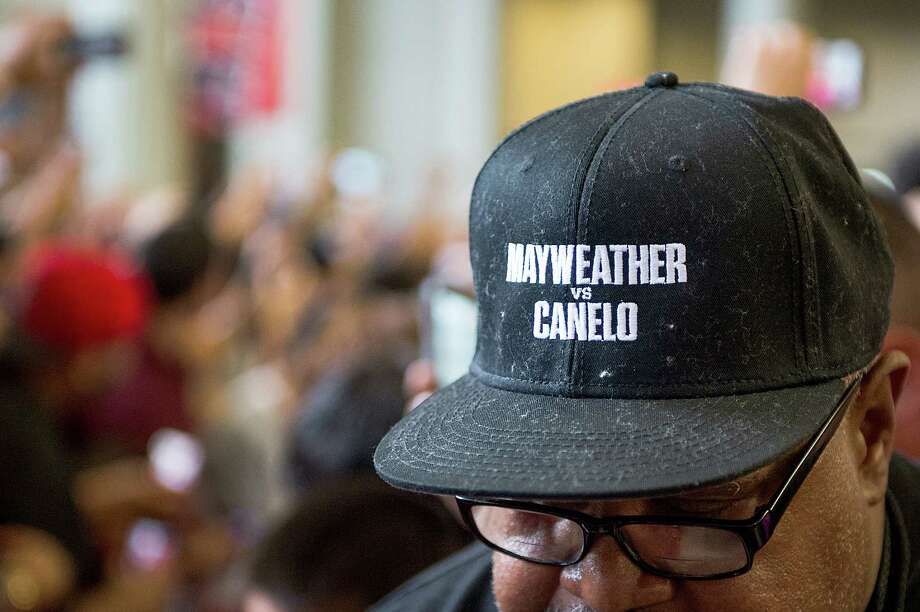 A man wears a hat promoting the fight. Photo: Smiley N. Pool, Houston Chronicle / © 2013  Houston Chronicle
