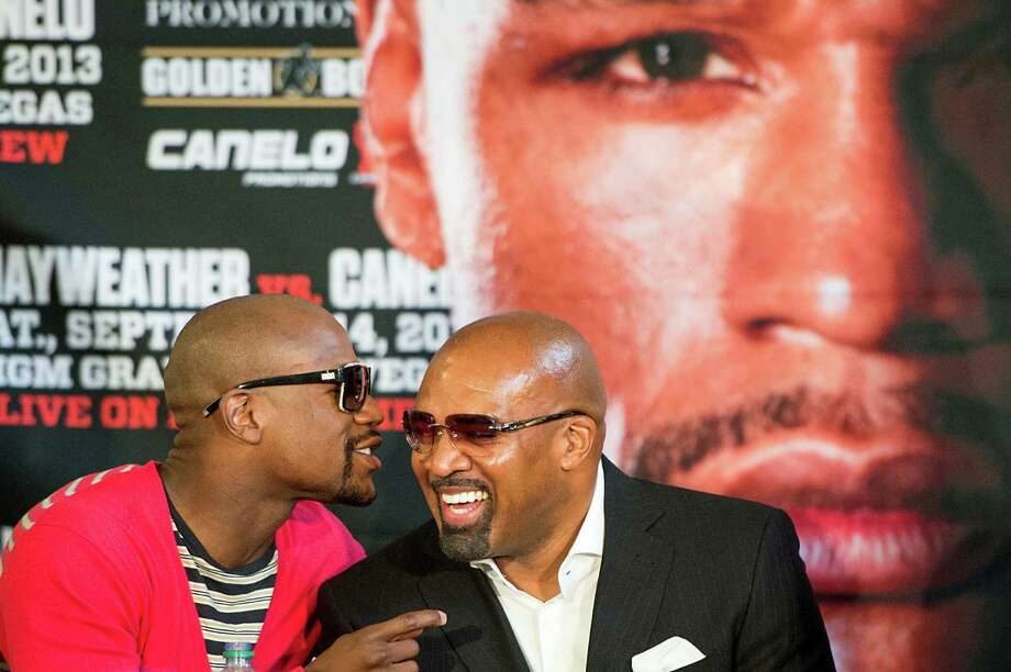 Boxer Floyd Mayweather, left, talks with Leonard Ellerbe. Photo: Smiley N. Pool, Houston Chronicle / © 2013  Houston Chronicle