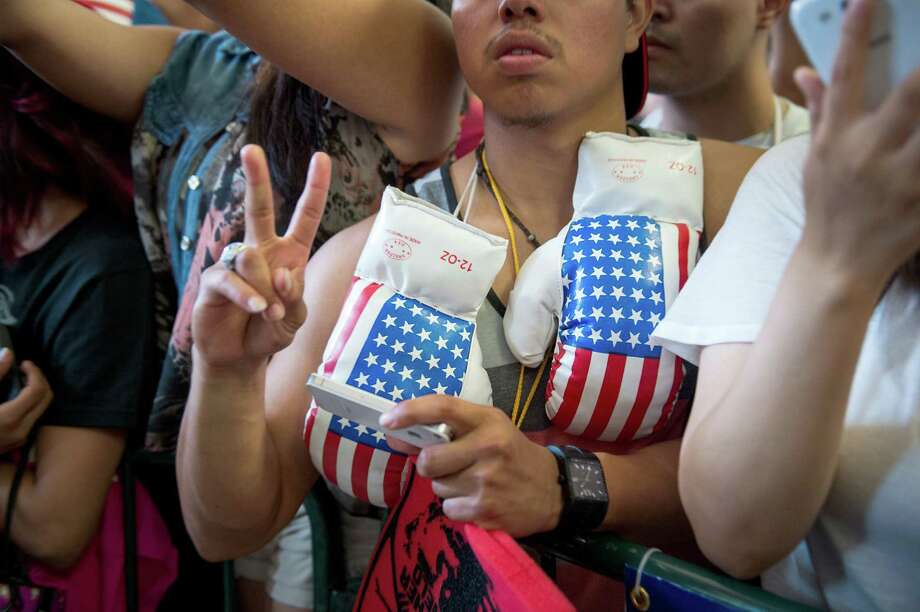 A fan waits with American flag boxing gloves hoping to get autographs. Photo: Smiley N. Pool, Houston Chronicle / © 2013  Houston Chronicle