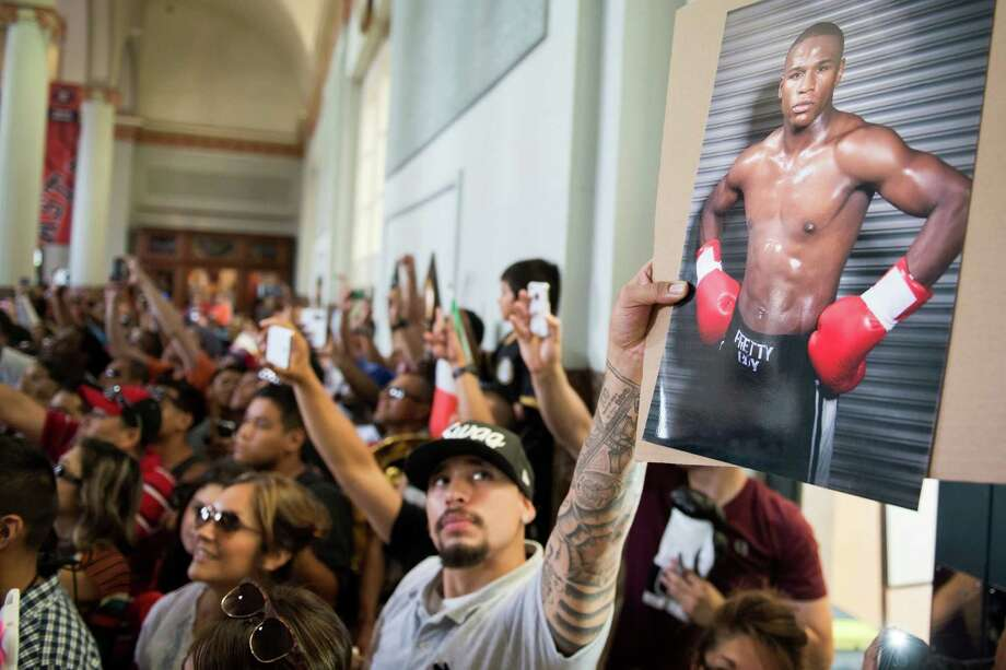 A fan holds up a photo of boxer Floyd Mayweather. Photo: Smiley N. Pool, Houston Chronicle / © 2013  Houston Chronicle