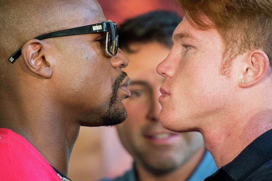 Boxers Floyd Mayweather and Canelo Alvarez face off during a promotional event as Oscar de la Hoya looks on at Minute Maid Park on Monday, July 1, 2013, in Houston.  The fighters made an appearance at Union Station as part of a tour to promote their Sept. 14 fight. Photo: Smiley N. Pool, Houston Chronicle / © 2013  Houston Chronicle