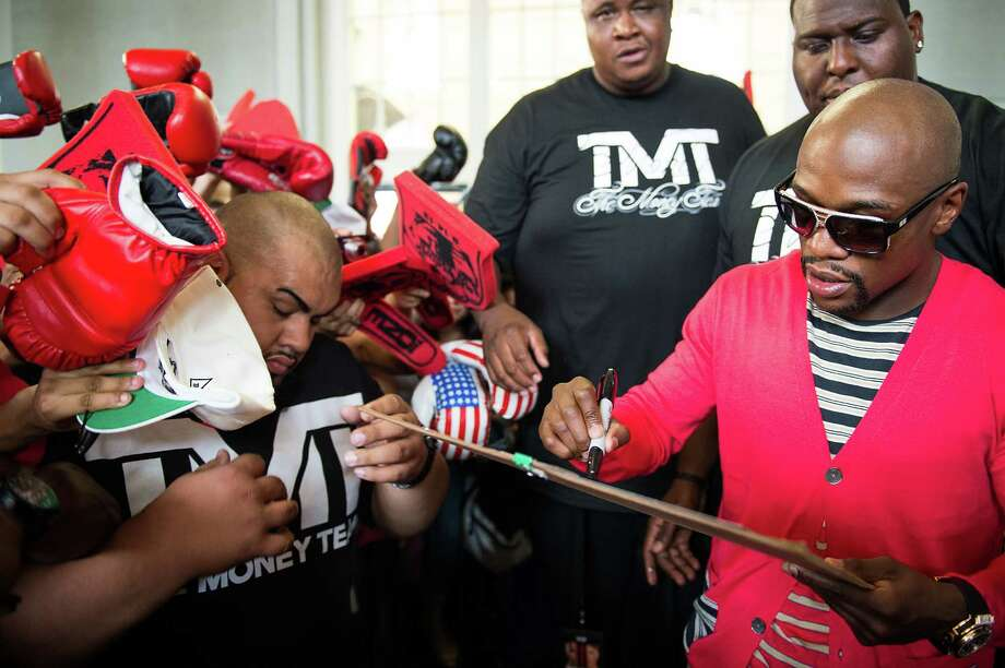 Security guards try to hold back the crowd as boxer Floyd Mayweather signs autographs. Photo: Smiley N. Pool, Houston Chronicle / © 2013  Houston Chronicle