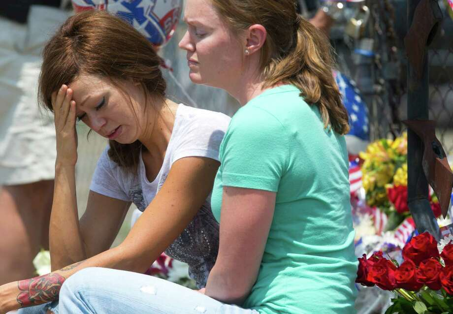 Juliann Ashcraft, left, of Prescott, the wife of Andrew Ashcraft, who was killed battling the Yarnell Hill Fire reacts as she sits by a memorial for the fallen firefighters in front of Prescott Fire Station #7 on Monday, July 1, 2013. Nineteen firefighters have died in the Yarnell Hill Fire that has ripped through half of the town and sent residents to Prescott for safety. (AP Photo/The Arizona Republic, David Wallace) Photo: David Wallace, Associated Press / The Arizona Republic