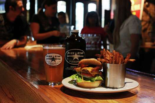 A bacon cheeseburger and french fries sit on the bar at the Blue Star Brewing Company