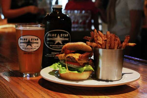 A bacon cheeseburger and french fries sit on the bar at the Blue Star Brewing Company on Tuesday, June 18, 2013.