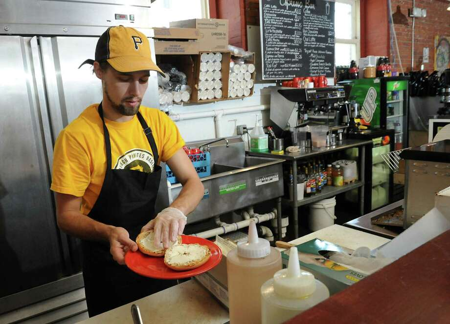 Anton Pasquill works behind the counter at the Hudson River Coffee House on Quail St. on Friday, June 21, 2013 in Albany, N.Y. With college students gone for the summer, he's experiencing slower business. (Lori Van Buren / Times Union) Photo: Lori Van Buren / 00022920A