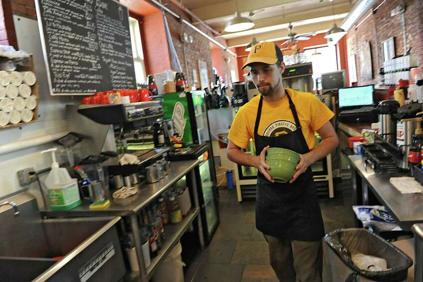Anton Pasquill works behind the counter at the Hudson River Coffee House on Quail St. on Friday, June 21, 2013 in Albany, N.Y. With college students gone for the summer, he's experiencing slower business. (Lori Van Buren / Times Union)
