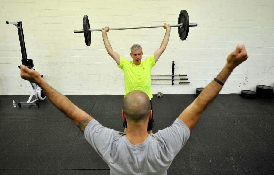 Co-owner Felipe Polanco, foreground, instructs Joe DiBuono on correct form during a one-hour Crossfit workout session at Iron Resolve Crossfit in Stamford on Monday, June 24, 2013. Photo: Jason Rearick / Stamford Advocate