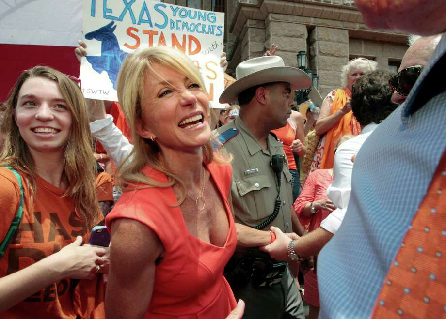 Texas Sen. Wendy Davis (D-Ft. Worth) is escorted into the Texas state capitol building after leading a rally in support of Texas women's right to reproductive decisions on July 1, 2013 in Austin, Texas. This is first day of a second legislative special session called by Texas Gov. Rick Perry to pass an restrictive abortion law through the Texas legislature. The first attempt was defeated after opponents of the law were able to stall the vote until after first special session had ended. Photo: Erich Schlegel, Getty Images / 2013 Getty Images