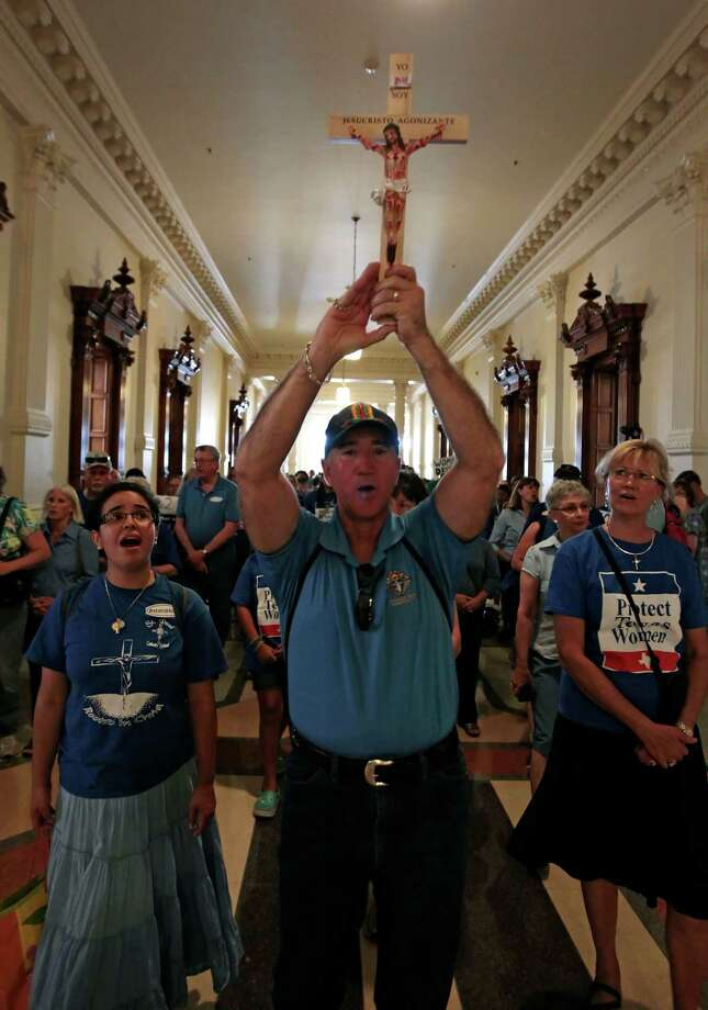 Michael Benavides of Austin holds up a crucifix and leads a group of pro-life supporters into the Texas State capitol on July 1, 2013 in Austin, Texas. This is first day of a second legislative special session called by Texas Gov. Rick Perry to pass an restrictive abortion law through the Texas legislature. The first attempt was defeated after opponents of the law were able to stall the vote until after first special session had ended. Photo: Erich Schlegel, Getty Images / 2013 Getty Images
