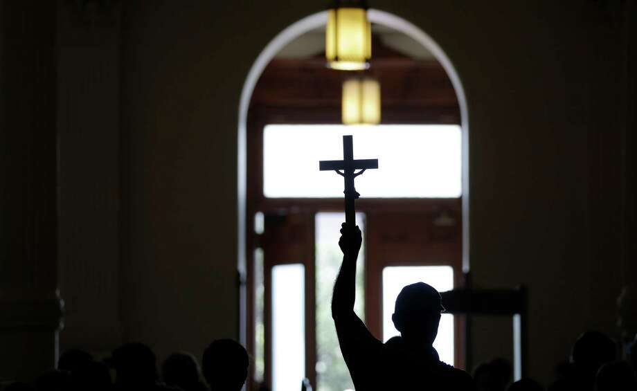An anti-abortion supporter carries a cross as he enters the Texas capitol, Monday, July 1, 2013, in Austin, Texas. The Texas Senate has convened for a new 30-day special session to take up a contentious abortion restrictions bill and other issues. Photo: Eric Gay, Associated Press / AP