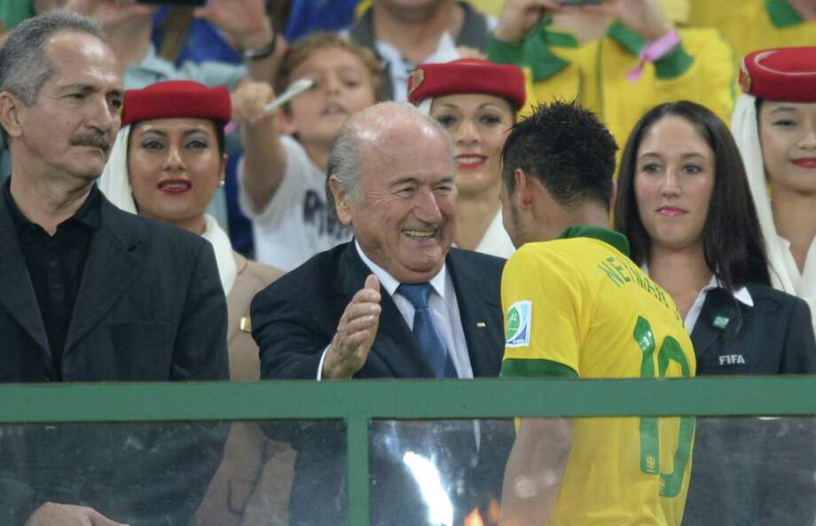 FIFA president Joseph Blatter (C) congratulates Brazil's forward Neymar moments before Brazil raises the trophy of the FIFA Confederations Cup Brazil 2013 football tournament after defeating Spain 3-0 in the final, at the Maracana Stadium in Rio de Janeiro on June 30, 2013. AFP PHOTO / VANDERLEI ALMEIDAVANDERLEI ALMEIDA/AFP/Getty Images ORG XMIT: 168637465 Photo: VANDERLEI ALMEIDA / Vanderlei Almeida