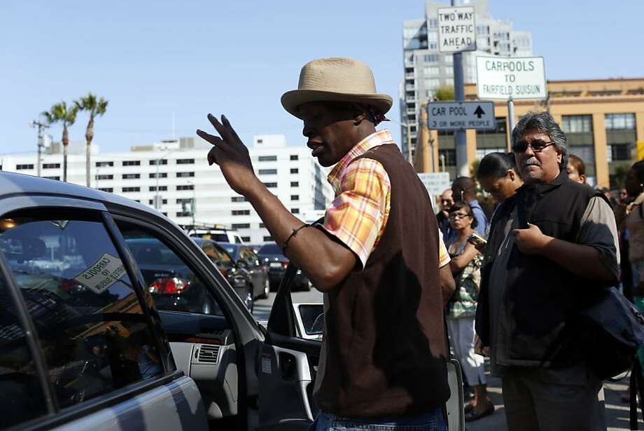 A man puts two fingers in the air gesturing for two more passengers to enter the car at carpool pickup stops on Beale Street while BART unions were on strike in San Francisco, Calif. on July 1, 2013. Photo: Ian C. Bates, The Chronicle
