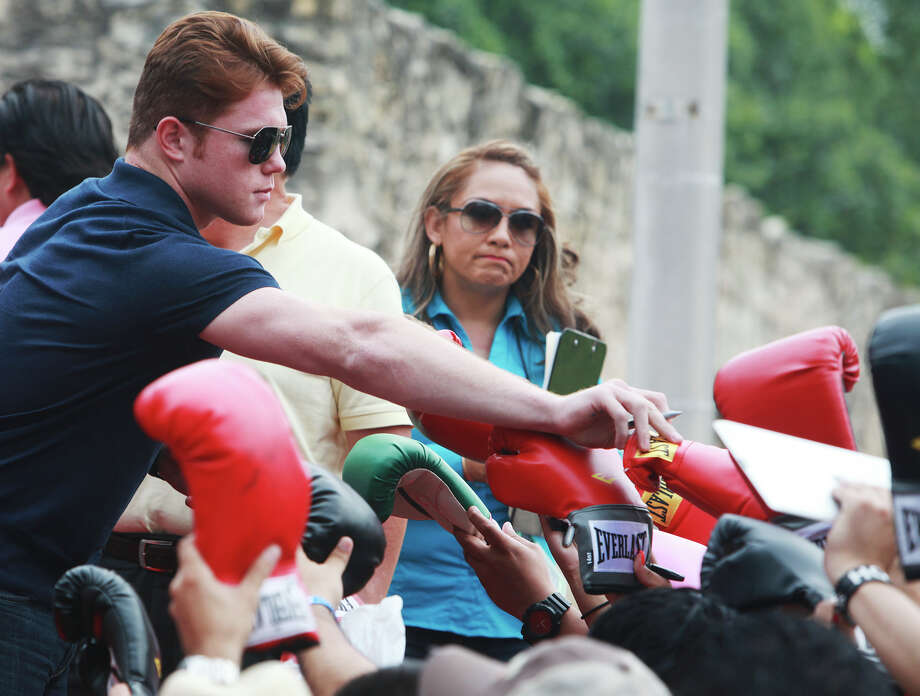 Canelo Alvarez reaches for a boxing glove in front of the Alamo on Monday, July 1, 2013. Photo: Abbey Oldham, San Antonio Express-News / San Antonio Express-News