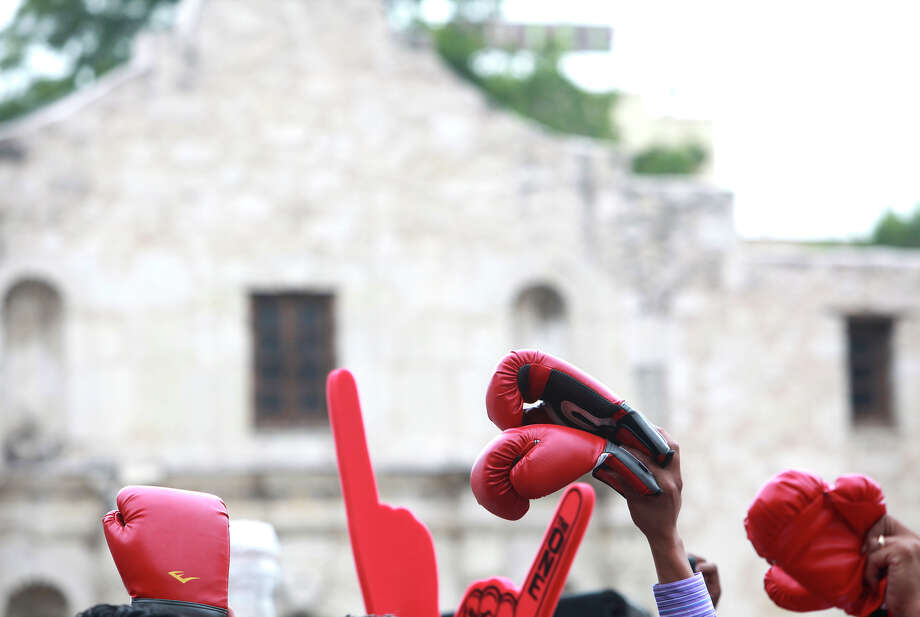 Fans hold gloves and foam fingers up to be signed by Canelo Alvarez in front of the Alamo on Monday, July 1, 2013.