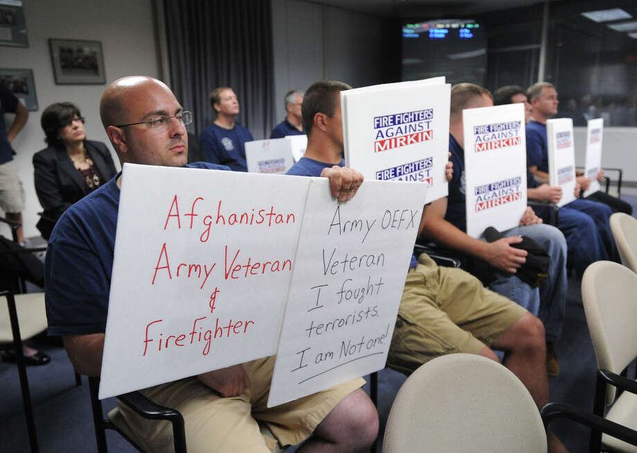 Joe Lombardo, left, along with fellow Stamford firefighters protest the mayor's nomination of Scott Mirkin to a seat on the Fire Commission during the Stamford Board of Representatives meeting at the Government Center on Monday, July 1, 2013. Photo: Jason Rearick / Stamford Advocate
