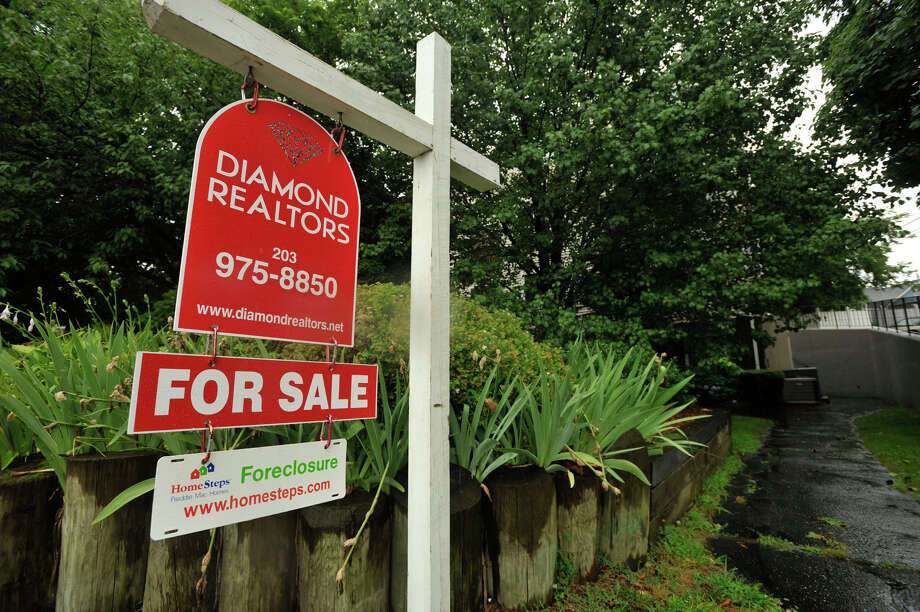 A foreclosure sign hangs below a for sale sign outside a property at 10 Fort Point Street in Norwalk on Monday, July 1, 2013. Photo: Jason Rearick / Stamford Advocate