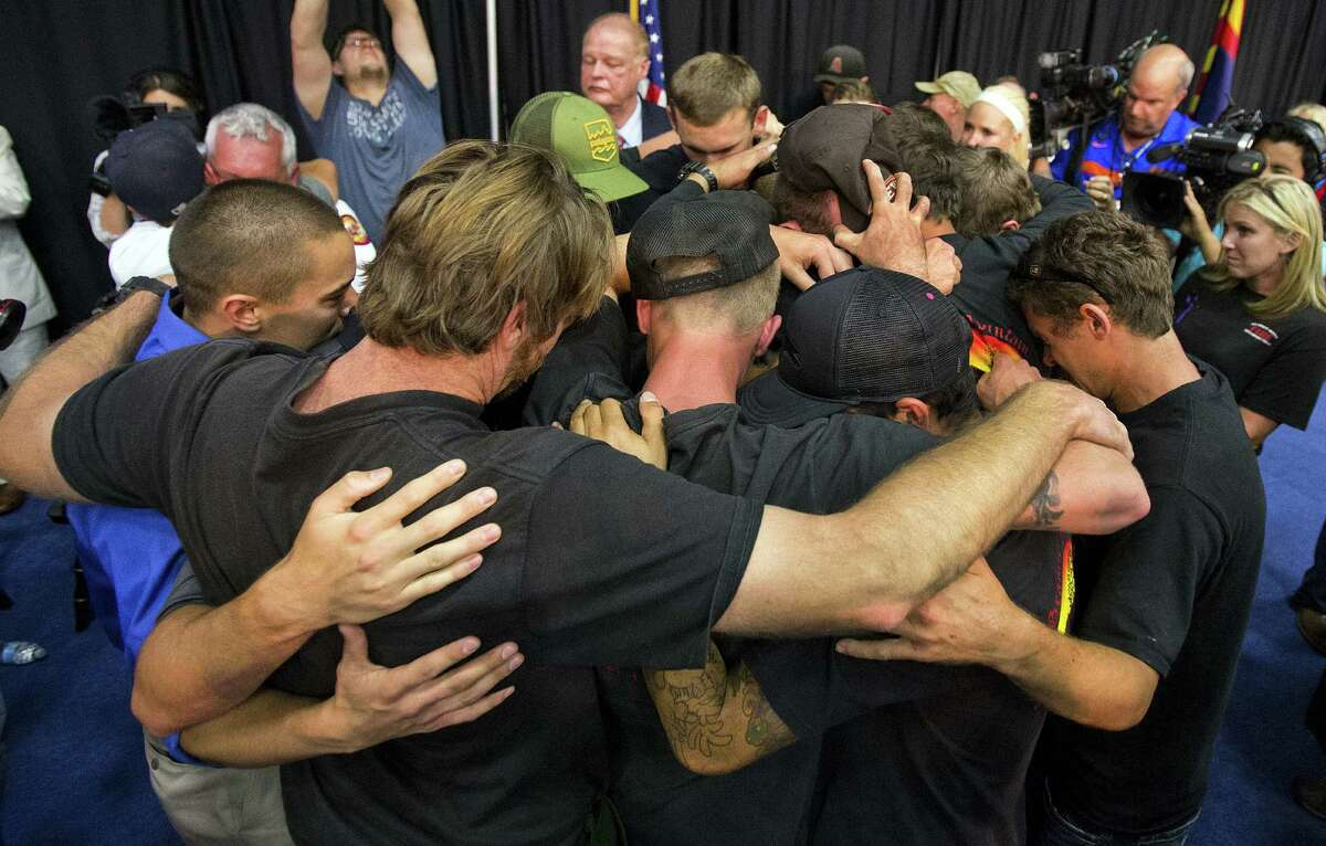 Firefighters gather in an embrace to a standing ovation during a memorial service for the 19 Granite Mountain Hotshot firefighters.