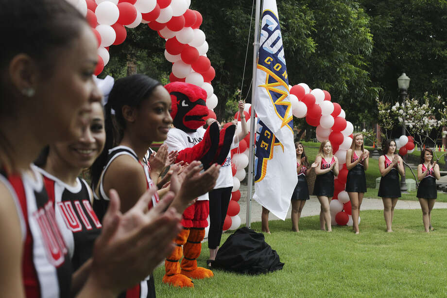 With the cheerleaders looking on, UIW raises a flag to commemorate its move to NCAA Division I and the Southland Conference. Photo: Abbey Oldham / San Antonio Express-News