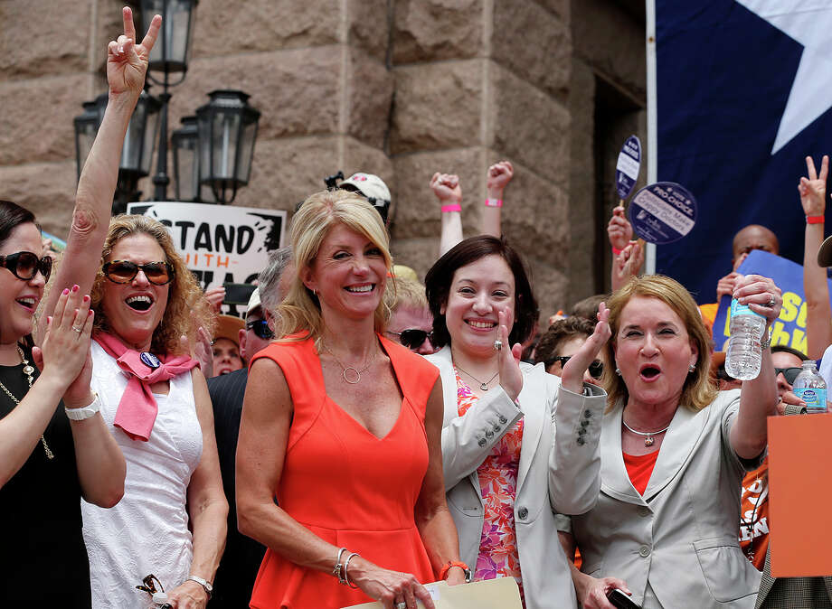 Senator Wendy Davis, third from left, smiles as she is introduced as the main speaker at the Stand With Texas Women Rally at State Capitol before the start of  the second special session, Monday, July 1, 2013. The anti-abortion legislation rally drew thousands of supporters. Photo: San Antonio Express-News / ©2013 San Antonio Express-News