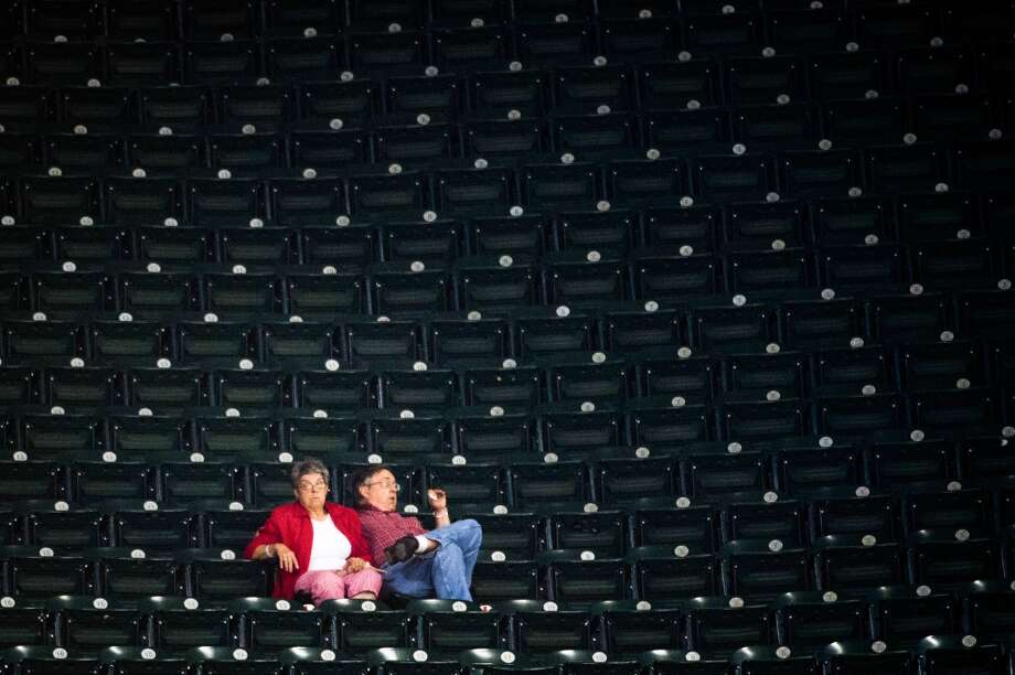 A pair of fans have an entire section to themselves as they watch the ninth inning of the Astros loss.