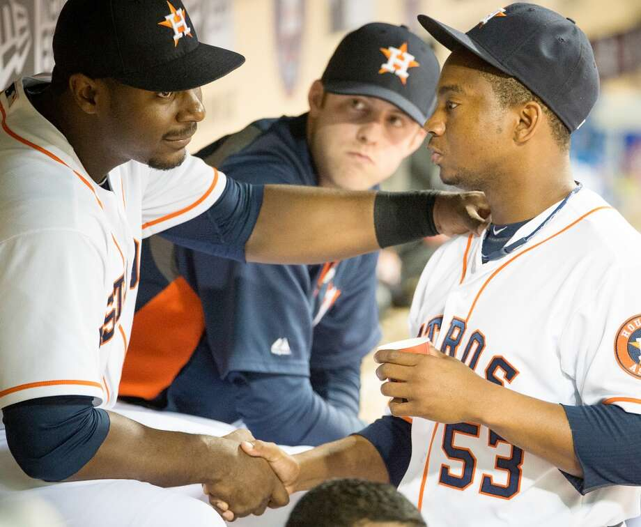 Astros relief pitcher Wesley Wright shakes hand with Chris Carter in the dugout after pitching the ninth.