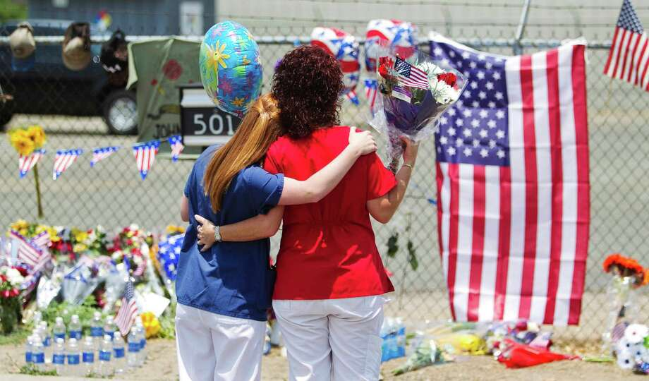 Carianne Sarvar, left, and Kathy Stapp, look over a makeshift memorial at the fire station Monday, July 1, 2013, in Prescott, Ariz., where an elite team of firefighters was based. Nineteen of the 20 members of the team were killed Sunday when a wildfire suddenly swept toward them in Yarnell, Ariz. Sarvar said her child attends the same daycare as one of the children of the fallen firefighters. (AP Photo/The Arizona Republic, Patrick Breen) Photo: Patrick Breen, Associated Press / The Arizona Republic
