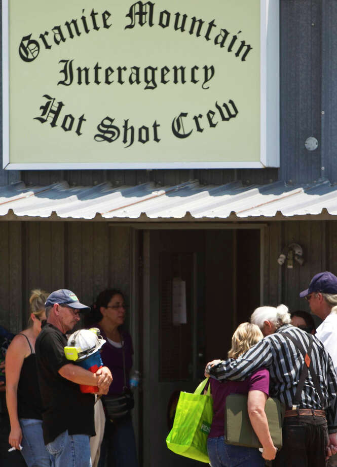 Families gather at Fire Station 7,  Monday, July 1, 2013, in Prescott, Ariz., where an elite team of firefighters was based. Nineteen of the 20 members of the team were killed Sunday when a wildfire suddenly swept toward them in Yarnell, Ariz. (AP Photo/The Arizona Republic, Patrick Breen) Photo: Patrick Breen, Associated Press / The Arizona Republic