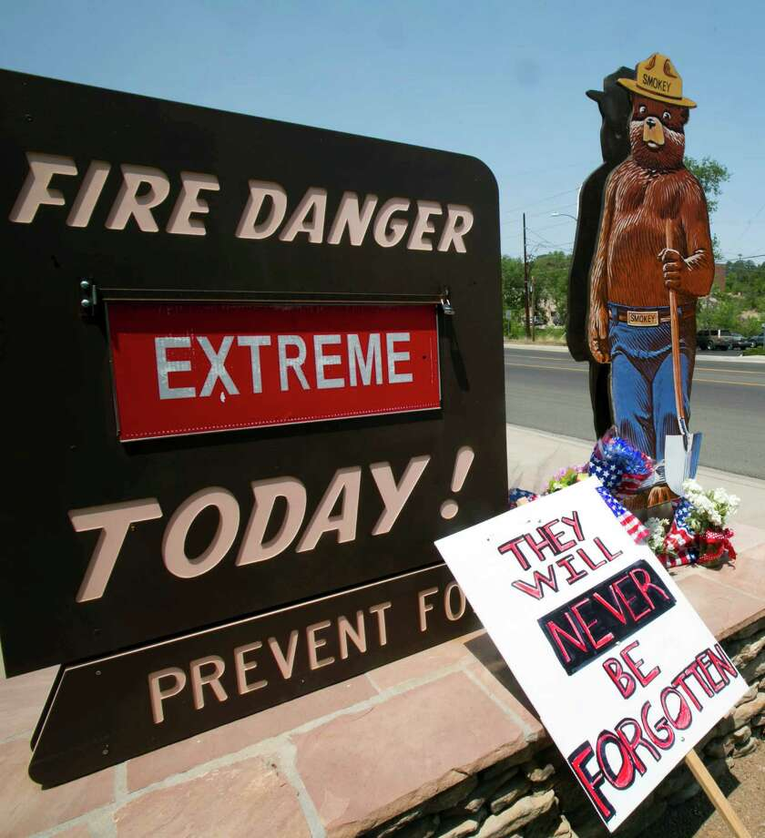 Signs are displayed at a makeshift memorial at the fire station Monday, July 1, 2013, in Prescott, Ariz., where an elite team of firefighters was based. Nineteen of the 20 members of the team were killed Sunday when a wildfire suddenly swept toward them in Yarnell, Ariz. (AP Photo/The Arizona Republic, Patrick Breen) Photo: Patrick Breen, Associated Press / The Arizona Republic