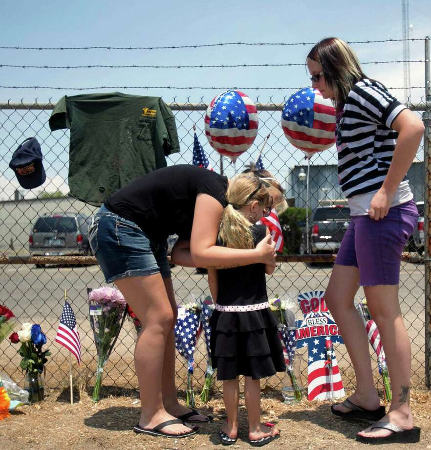 Angela Clark, left, her daughter Chloe, middle, and Theresa Winquest visit a makeshift memorial at the fire station Monday, July 1, 2013, in Prescott, Ariz., where an elite team of firefighters was based. Nineteen of the 20 members of the team were killed Sunday when a wildfire suddenly swept toward them in Yarnell, Ariz. (AP Photo/The Arizona Republic, Patrick Breen) Photo: Patrick Breen, Associated Press / The Arizona Republic
