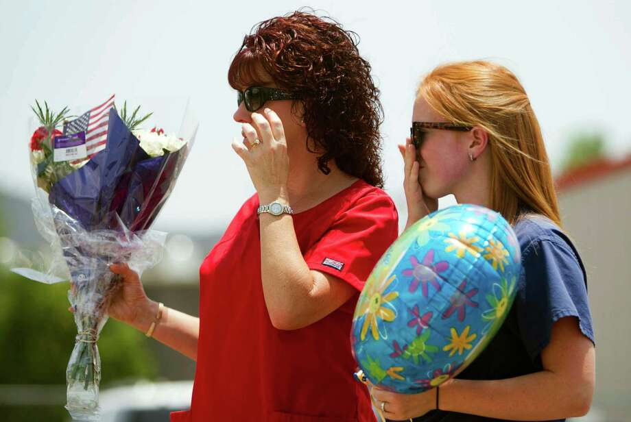 Carianne Sarvar, right, and Kathy Stapp, look over a makeshift memorial at the fire station Monday, July 1, 2013, in Prescott, Ariz., where an elite team of firefighters was based. Nineteen of the 20 members of the team were killed Sunday when a wildfire suddenly swept toward them in Yarnell, Ariz. Sarvar said her child attends the same daycare as one of the children of the fallen firefighters. (AP Photo/The Arizona Republic, Patrick Breen) Photo: Patrick Breen, Associated Press / The Arizona Republic