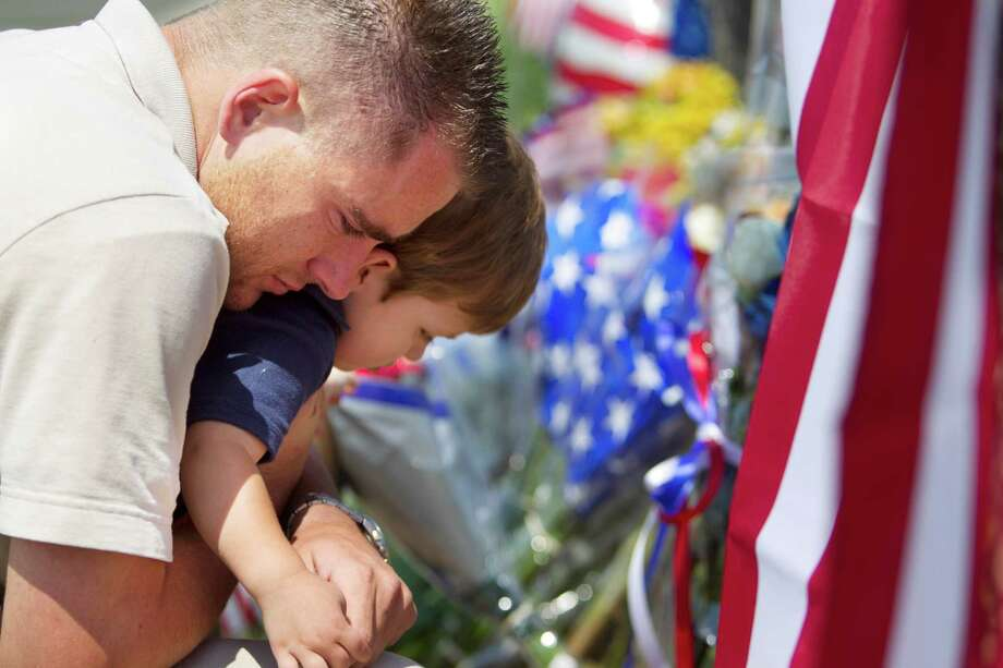Duane Oliver of Prescott Valley hugs his son, Conner Oliver, 2, by a memorial for the fallen firefighters in front of Prescott Fire Station #7 on Monday, July 1, 2013. Nineteen firefighters have died in the Yarnell Hill Fire that has ripped through half of the town and sent residents to Prescott for safety. (AP Photo/The Arizona Republic, David Wallace) Photo: David Wallace, Associated Press / The Arizona Republic