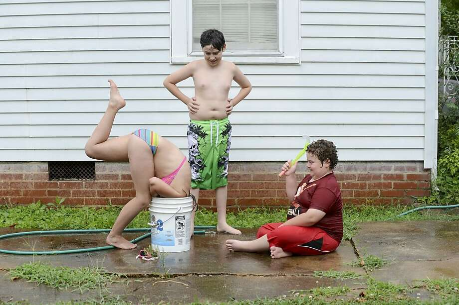 Hey, no diving allowed! Savannah Knox takes a dip in a low-budget above-ground pool her stepbrothers, Dregan and D.J. Rucker, just filled up in Decatur, Ala. Photo: John Godbey, Associated Press