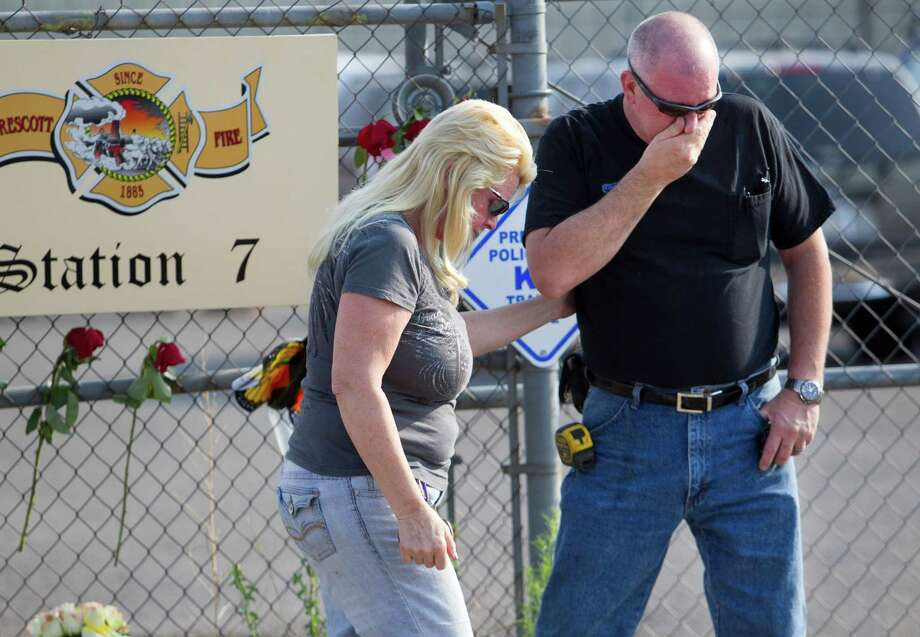 David Turbyfill of Prescott, the father of Travis Turbyfill, who was killed fighting the Yarnell Hill Fire is comforted by his wife, Shari Turbyfill (not Travis' mother) in front of Prescott Fire Station #7 on Monday, July 1, 2013. Nineteen firefighters have died in the Yarnell Hill Fire that has ripped through half of the town and sent residents to Prescott for safety. (AP Photo/The Arizona Republic, David Wallace) Photo: David Wallace, Associated Press / The Arizona Republic