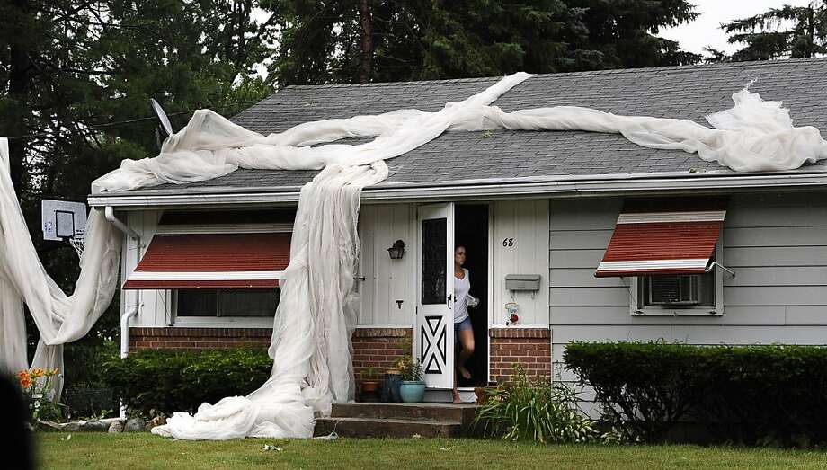 Tobacco netting is seen on top of a home in a neighborhood in Windsor Locks after a powerful storm, possibly producing a tornado, tore through the towns of Windsor Locks and East Windsor, Conn., Monday, July 1, 2013. (AP Photo/Journal Inquirer, Jessica Hill) MANDATORY CREDIT Photo: Jessica Hill, Associated Press