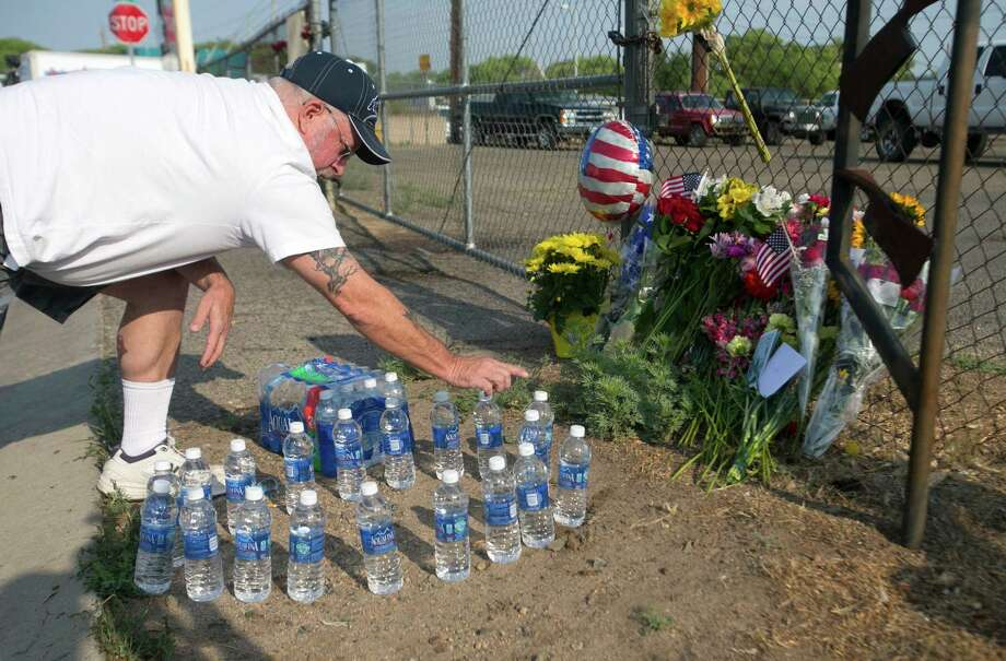 Keith Gustafson, of Prescott, counts out 19 bottles of water he just placed at a memorial in front of Prescott Fire Station #7 on Monday, July 1, 2013. Nineteen firefighters have died in the Yarnell Hill Fire that has ripped through half of the town and sent residents to Prescott for safety. (AP Photo/The Arizona Republic, David Wallace) Photo: David Wallace, Associated Press / The Arizona Republic