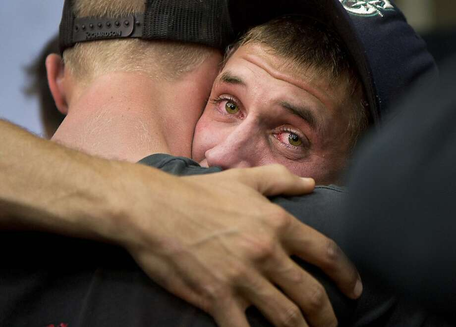 Prescott and other area department firefighters embrace during a memorial service, Monday, July 1, 2013 in Prescott, Ariz., The service was held for the 19 Granite Mountain Hotshot Crew firefighters who were killed Sunday, when an out-of-control blaze overtook the elite group. (AP Photo/Julie Jacobson) Photo: Julie Jacobson, Associated Press