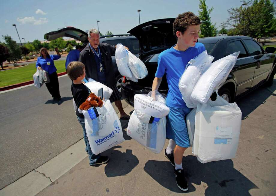 Tara Reyes,  Kevin Ray, Pastor Tim Parker, Markis Youoston and T.J. Youoston carry donated supplies from Walmart to the Red Cross Shelter for those affected by the Yarnell Hill Fire on Monday, July 1, 2013 in Prescott, Ariz.  (AP Photo/The Arizona Republic, David Kadlubowski) Photo: David Kadlubowski, Associated Press / The Arizona Republic