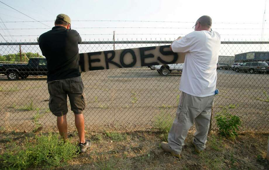 Two men place a hero sign in front of Prescott Fire Station #7 on Monday, July 1, 2013, in Prescott, Ariz.  Eighteen firefighters from the Prescott Fire Department's Granite Mountain Hotshots team and a 19th firefighter from another crew were killed battling the Yarnell Hill Fire on Sunday. The Granite Mountain Hotshots were based out of Prescott Fire Station #7. David Wallace/The Arizona Republic  (AP Photo/The Arizona Republic, Dasvid Wallace)  MARICOPA COUNTY OUT; MAGS OUT; NO SALES Photo: David Wallace, Associated Press / The Arizona Republic